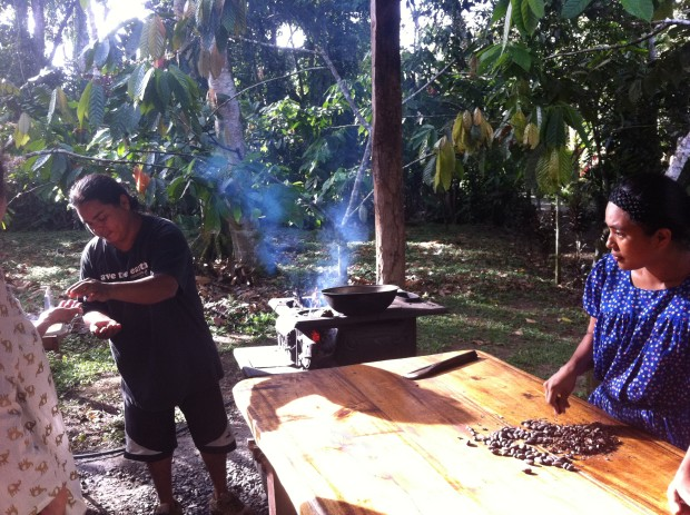 Rafael Obando hands out samples of roasted cocoa as Eunice cracks open the beans.