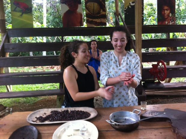 Rebecca Ureña, left and her sister, Amanda, visitors from New York, knead chocolate into balls as mother Linda looks on.