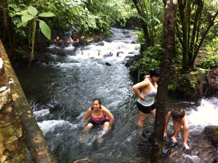 Visitors soak in the hot Río Chollín near Arenal Volcano.