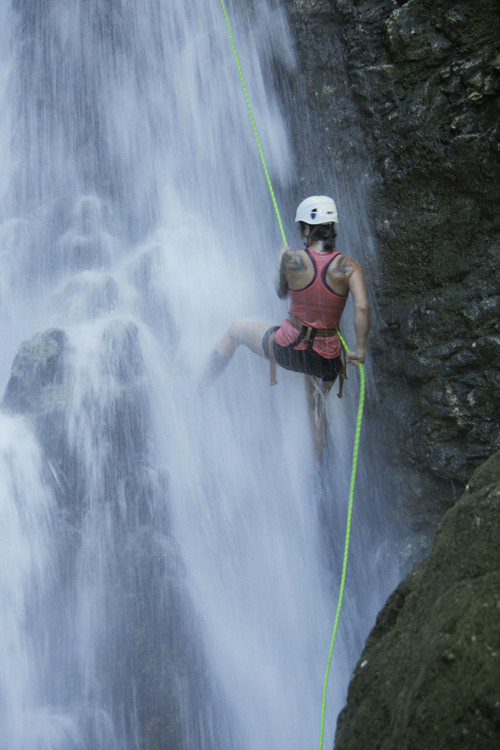 A woman rappels down a 40-foot waterfall in Matapalo.