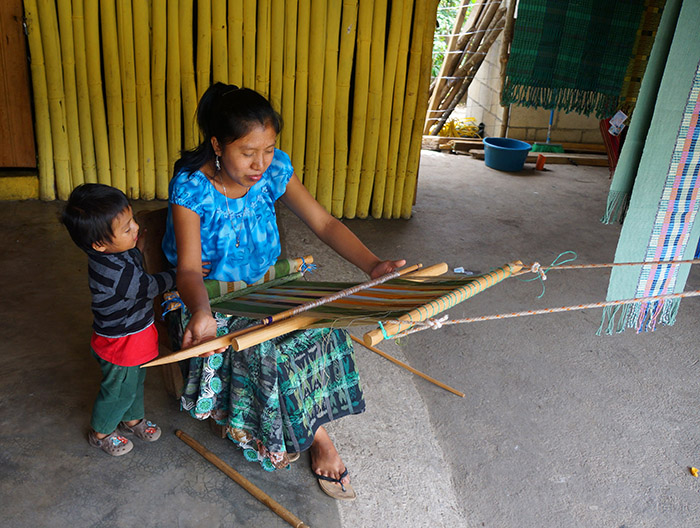A local woman weaves textiles in the village of San Juan.