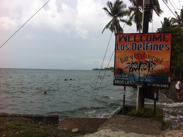 Swimmers at the public beach in front of Los Delfines Restaurant at high tide.