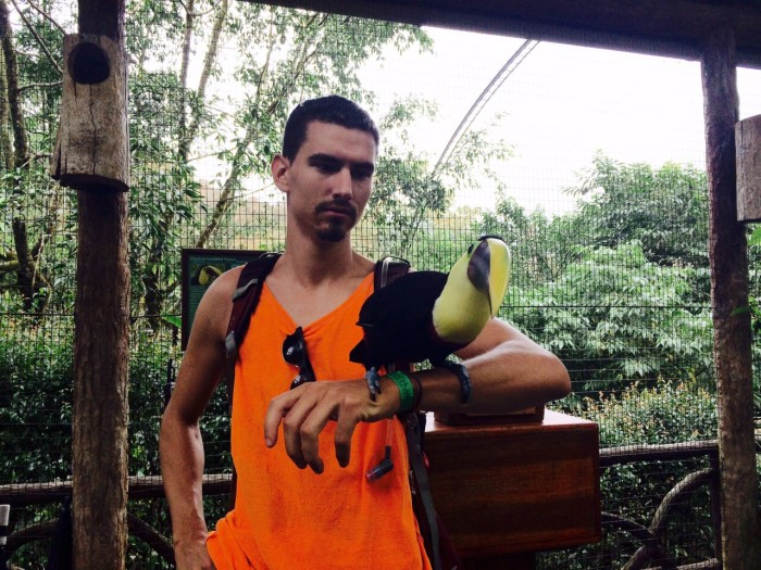 The writer poses with a friendly toucan that roams the grounds of La Paz Waterfall Gardens.