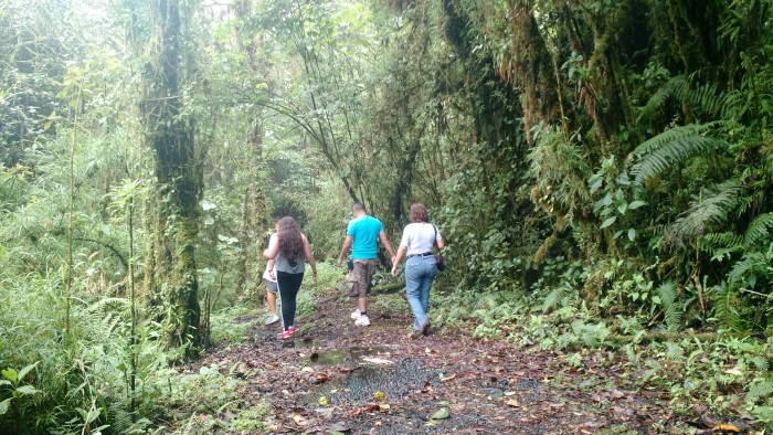 A family braves the muddy trail towards Copey Lagoon on Barva Volcano.