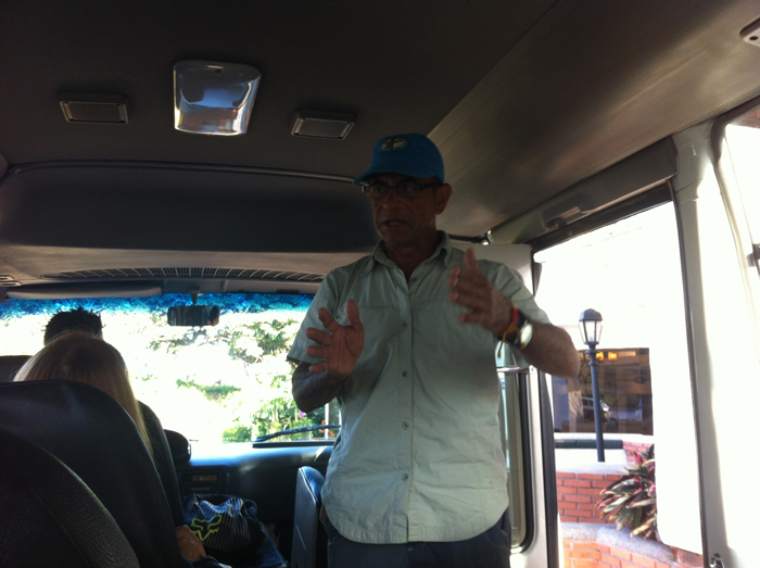 Mario Davis tells stories to a dozen people on a bus to Tortuguero.