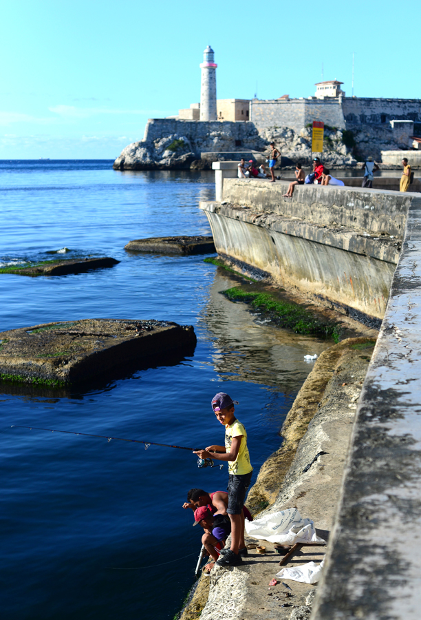 Families fish in front of the Morro Castle on Havana's Malecón.