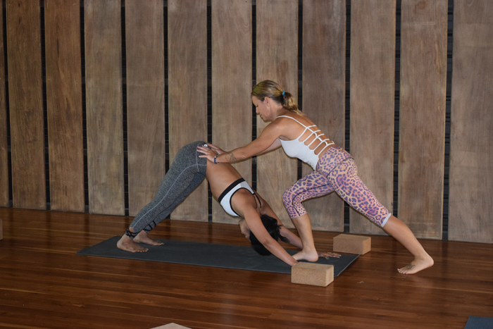 Yali McGregor works with a student in a yoga class at the Bodhi Tree.