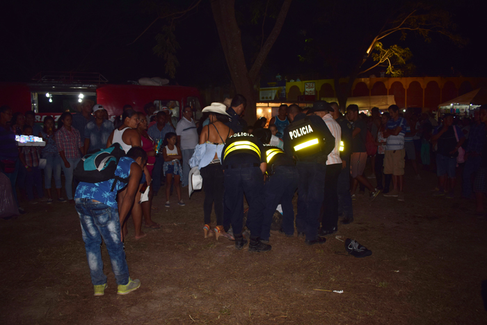 Because life is not fair, police detain a man at the Fiestas de Nosara after a fight between two women.