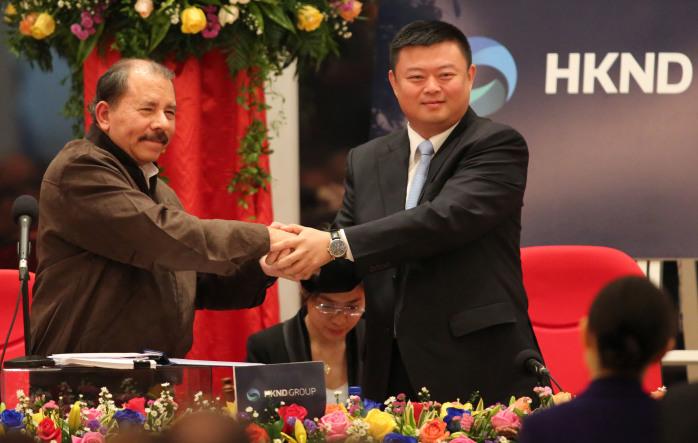 Nicaraguan President Daniel Ortega, left, shakes hands with Wang Jing.