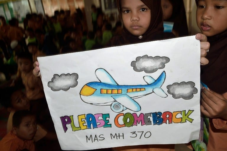 An Indonesian student displays a message expressing prayers and well-wishes for passengers of the missing Malaysia Airlines flight MH370, in Medan, North Sumatra on March 15, 2014.