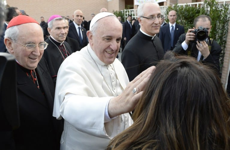 Pope Francis blesses a woman as he is welcomed by faithfuls while arriving for a visit to the parish of San Tommaso on the outskirts of Rome on Feb. 16, 2014.