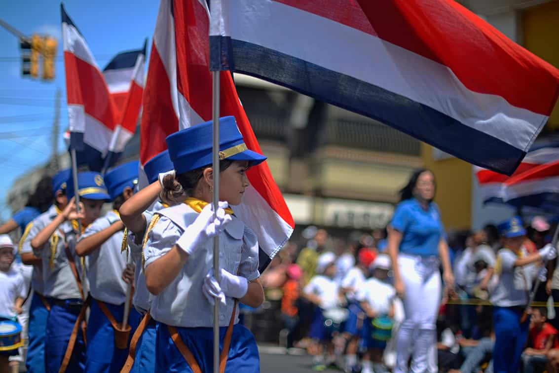 Children carry Costa Rican flags during Alajuela's Juan Santamaría Day parade in 2014.