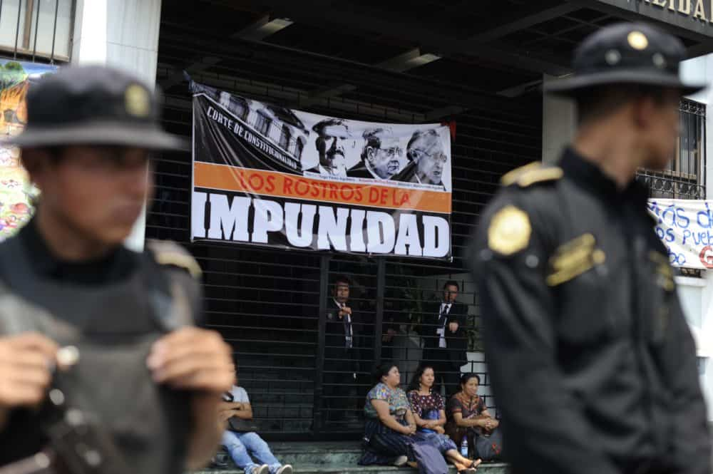 Police guard the entrance of the Constitutional Court of Guatemala during a protest against the quashing of the 80-year sentence for genocide of former Guatemalan dictator General Efrain Ríos Montt on May 24, 2013 in Guatemala City.