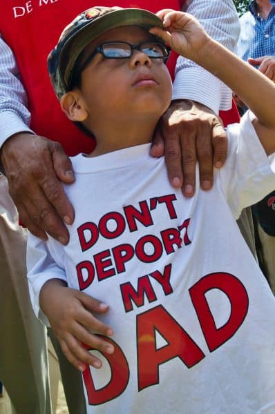 A young boy joins faith leaders and activists in a protest against immigrant deportations in front of the White House in Washington, D.C., on July 31, 2014.
