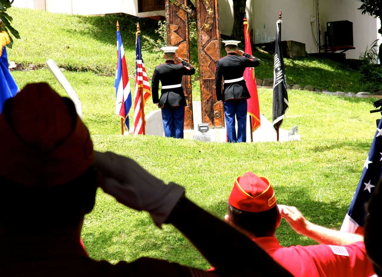 Current and veteran U.S. marines salute the flag at a ceremony commemorating the events of Sept. 11, 2001