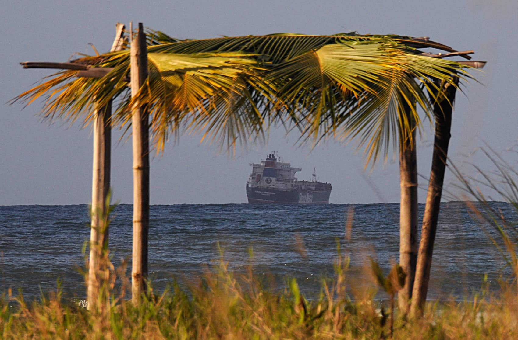 A makeshift beach hut frames a cargo ship waiting to dock at Costa Rica's Moín Port.