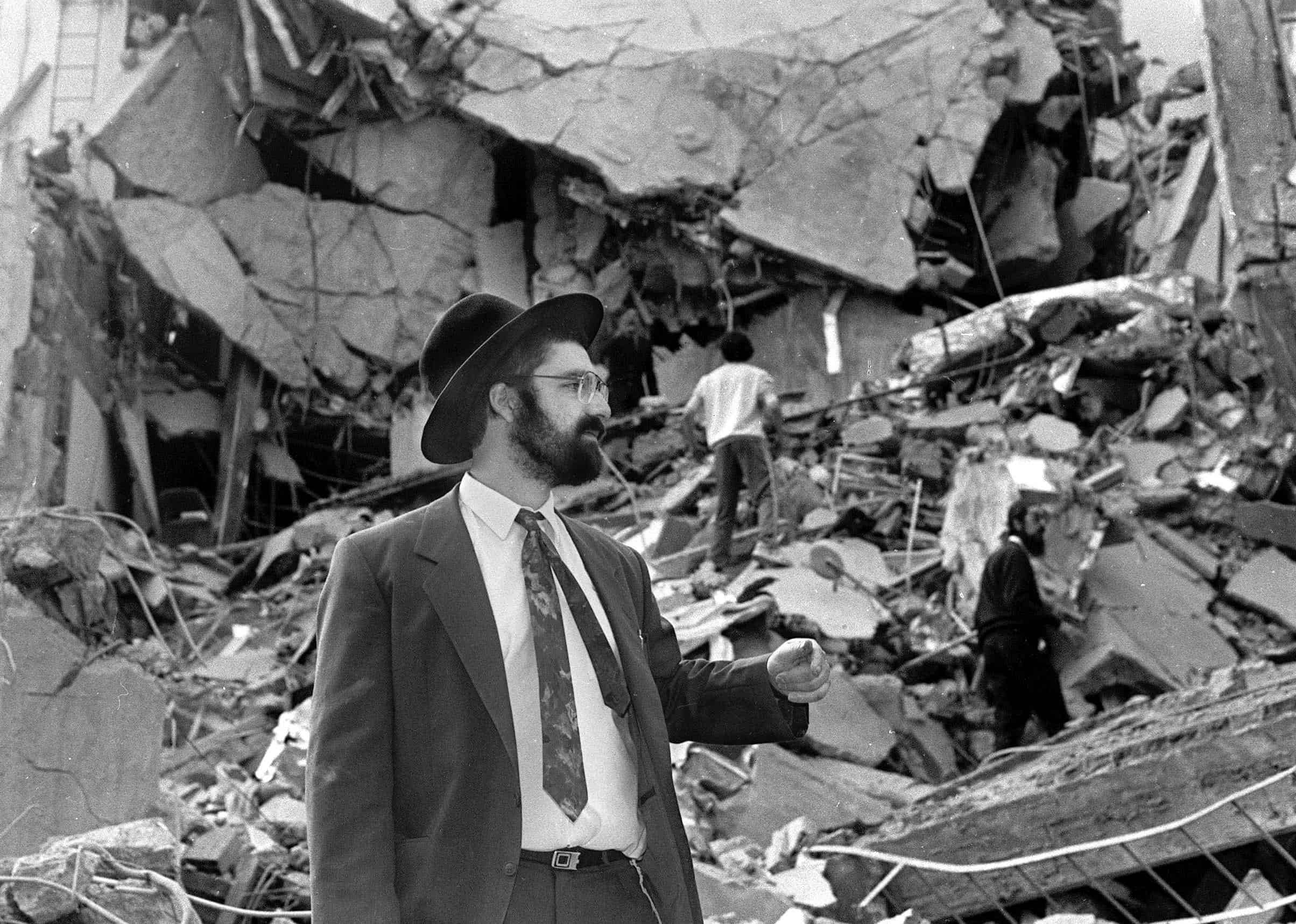 A man walks over rubble after a bomb exploded at the Argentine Israelite Mutual Association (AMIA) in Buenos Aires, on July 18, 1994, killing 85 people and injuring 300 others in the worst attack of its kind in the South American country.