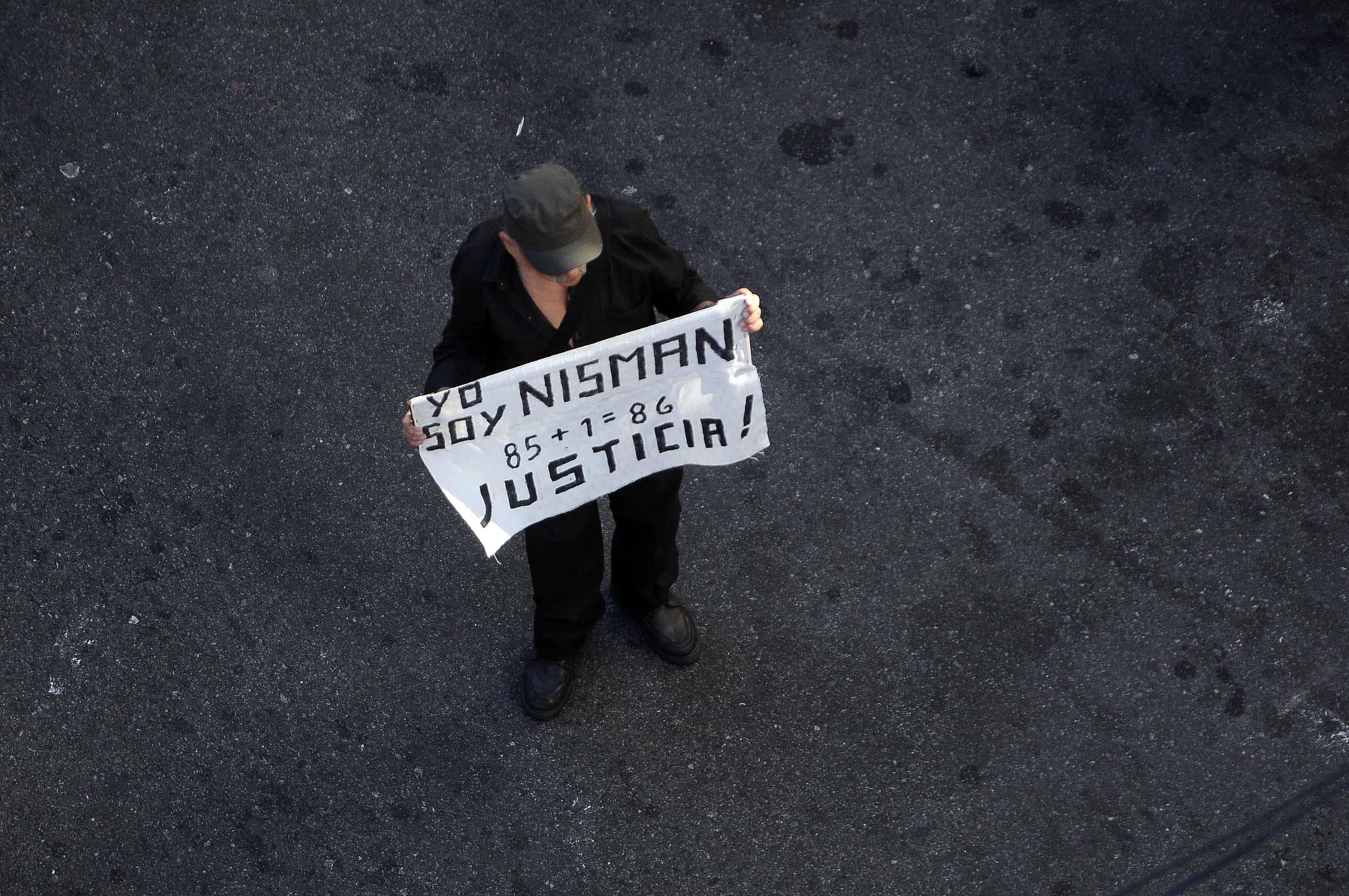 "A man holds a placard that reads ""I am Nisman, 85+1, Justice"" during a rally in front of the headquarters of the AMIA (Argentine Israelite Mutual Association), in Buenos Aires on Jan. 21, 2015."