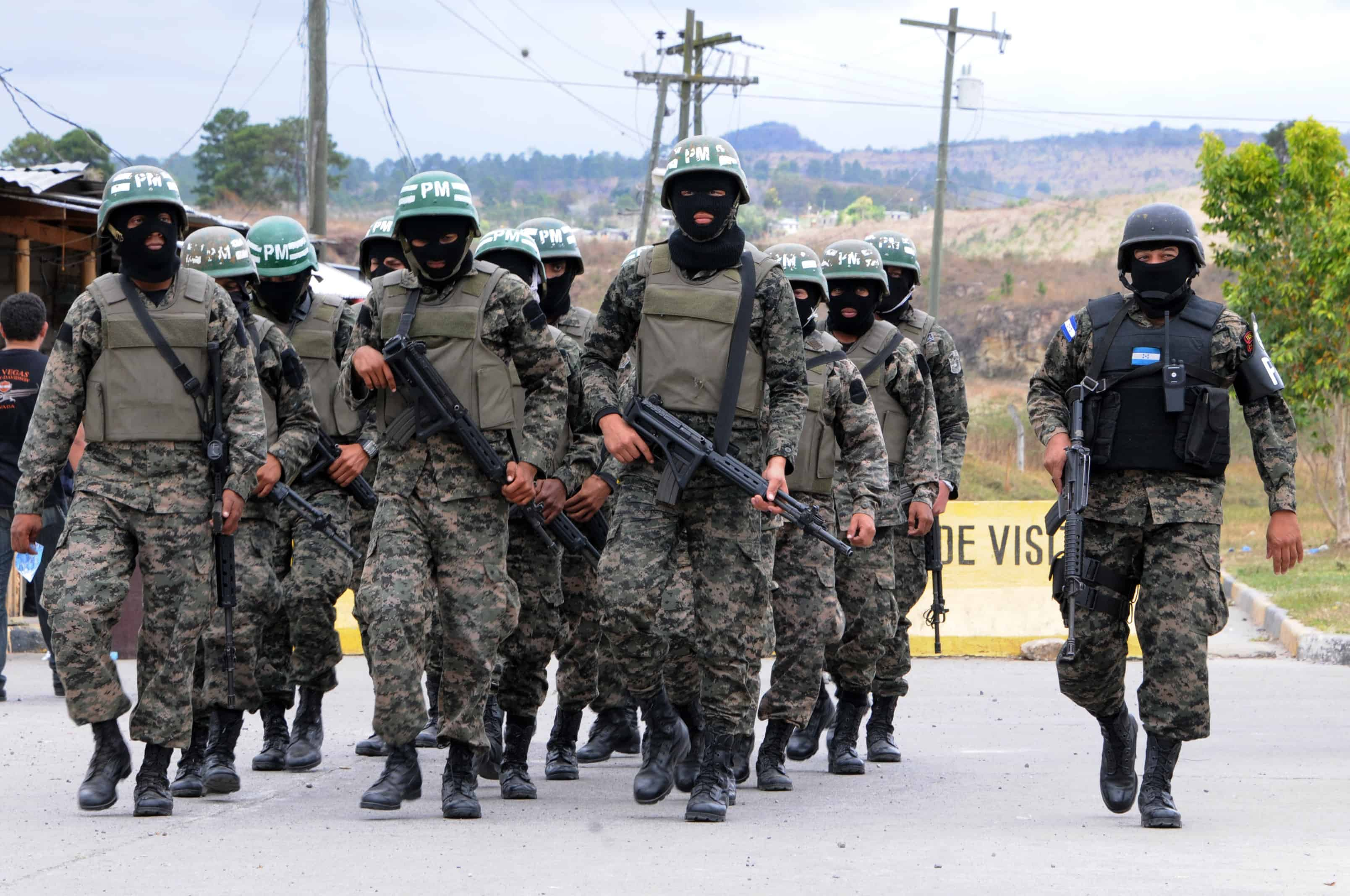 Members of the Honduran military police walk toward the Marco Aurelio Soto National Penitentiary to search for weapons, drugs and cell phones in Valle en Tamara, 25kms north of Tegucigalpa, on Febraury 25, 2014.