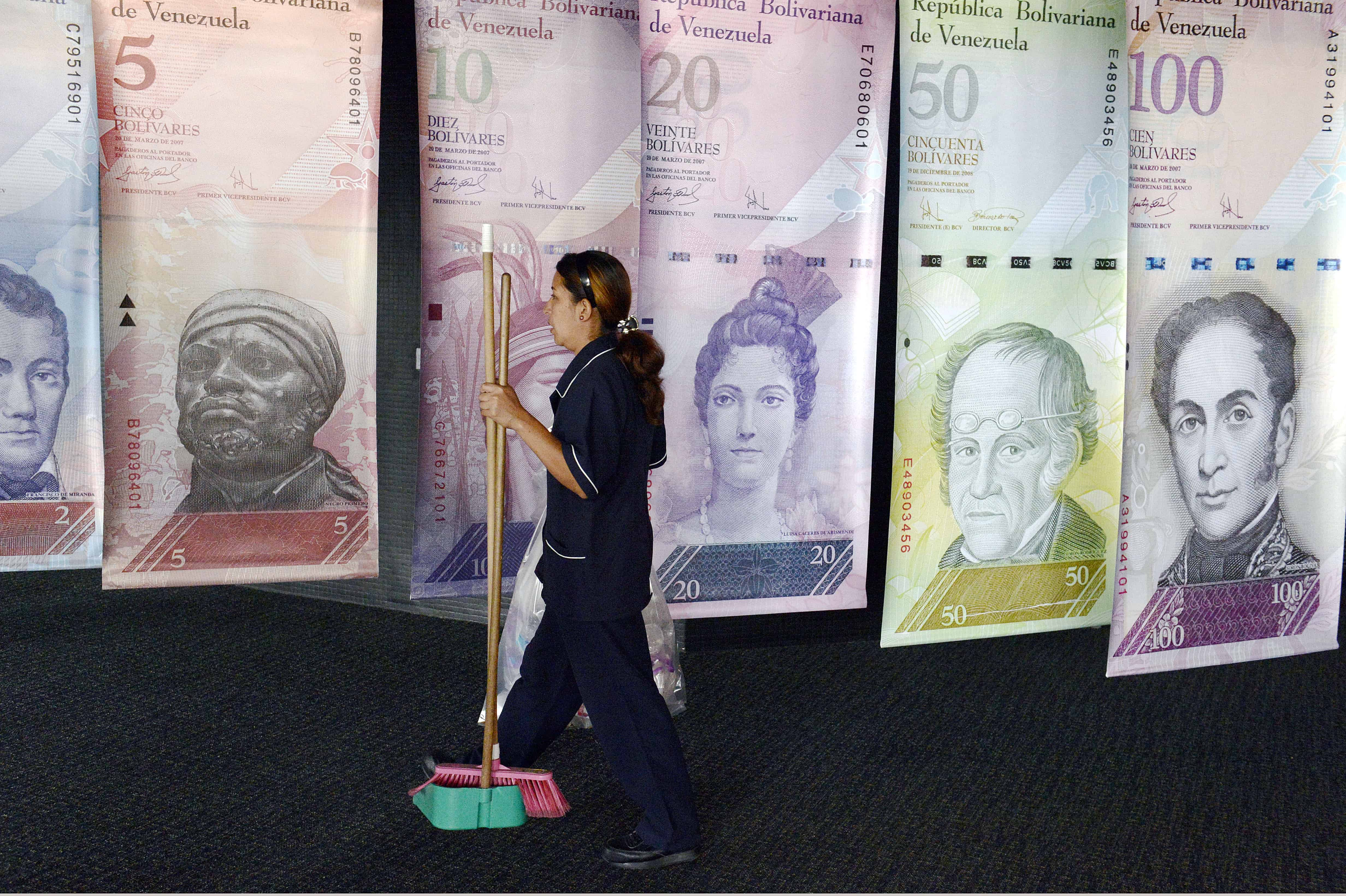 A woman walks past banners portraying the Venezuelan currency, the Bolivar, at the Venezuelan Central Bank in Caracas on February 10, 2015.