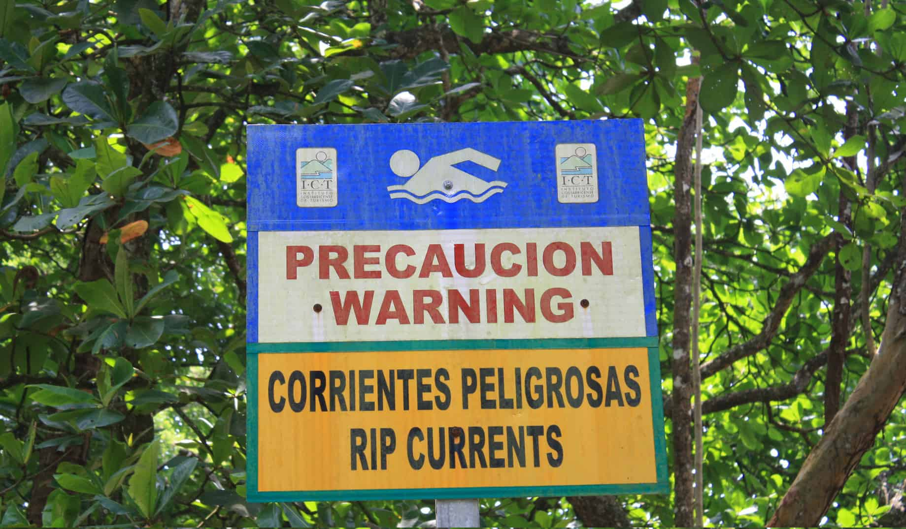 Sign warns of rip currents at Playa Cocles on the southern Caribbean coast, one of the few beaches in Costa Rica that has a lifeguard tower.