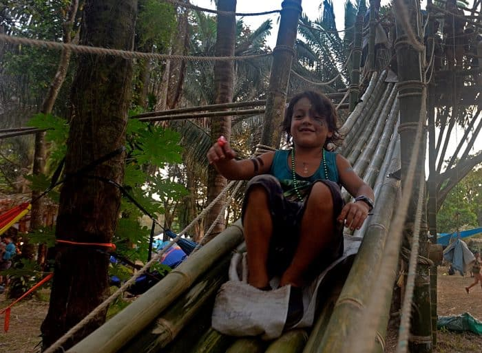 A child heads down the bamboo slide in the Envision village.