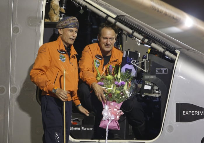 Swiss pilots Bertrand Piccard (wearing a traditional Omani turban) and Andre Borschberg pose for pictures during an official welcome after Solar Impulse 2 landed in the Omani capital Muscat on March 9, 2015.