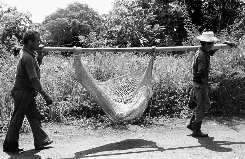 A casualty of the Salvadoran Civil War is carried back to his farm for burial, 1982.