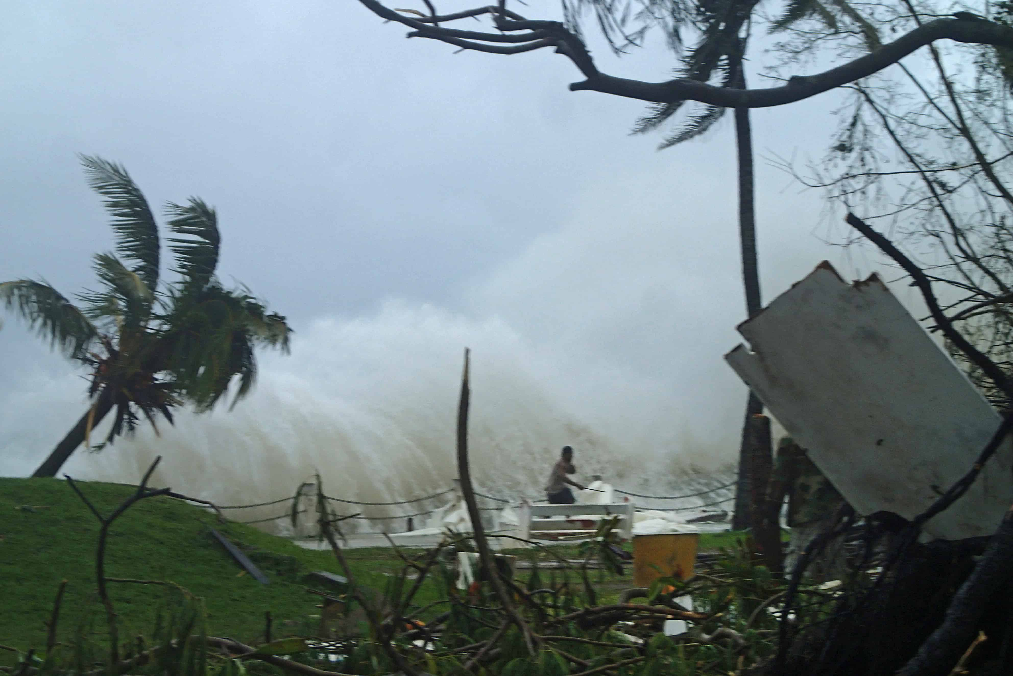 This handout photo taken on March 14, 2015 and received on March 15 by CARE Australia shows a man running away from high waves caused by Cyclone Pam crashing along the coast in the Vanuatu capital of Port Vila.