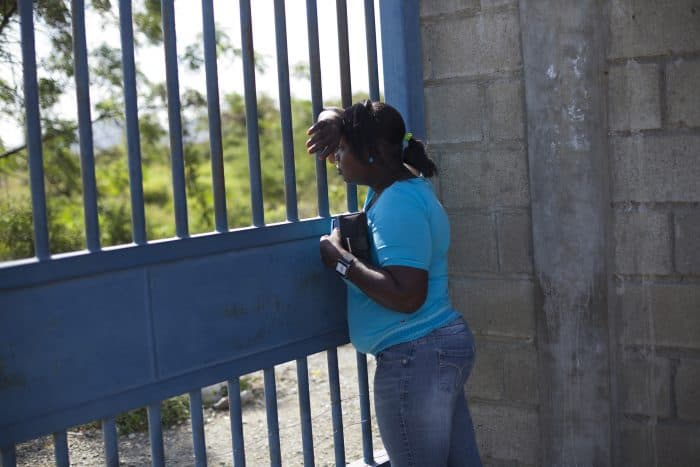 Job seeker Hermain Jean Pierre looks through the gate of the Caracol Industrial Park, in Caracol, Haiti.