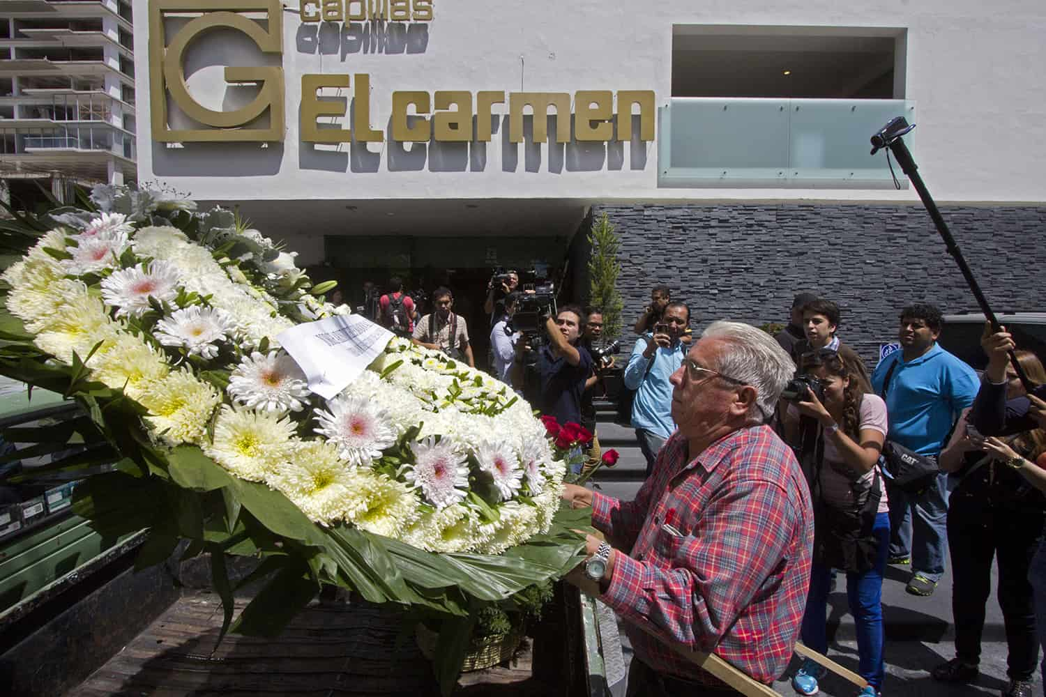 """A man delivers a wreath during the funeral of professional wrestler Pedro Aguayo Ramirez aka """"Perro Aguayo Jr"""" in Guadalajara city on March 22, 2015."""