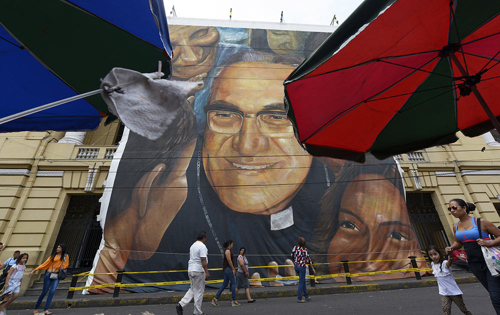 A man walks in front of a giant banner with the picture of Archbishop Oscar Romero in San Salvador, on March 22, 2015.