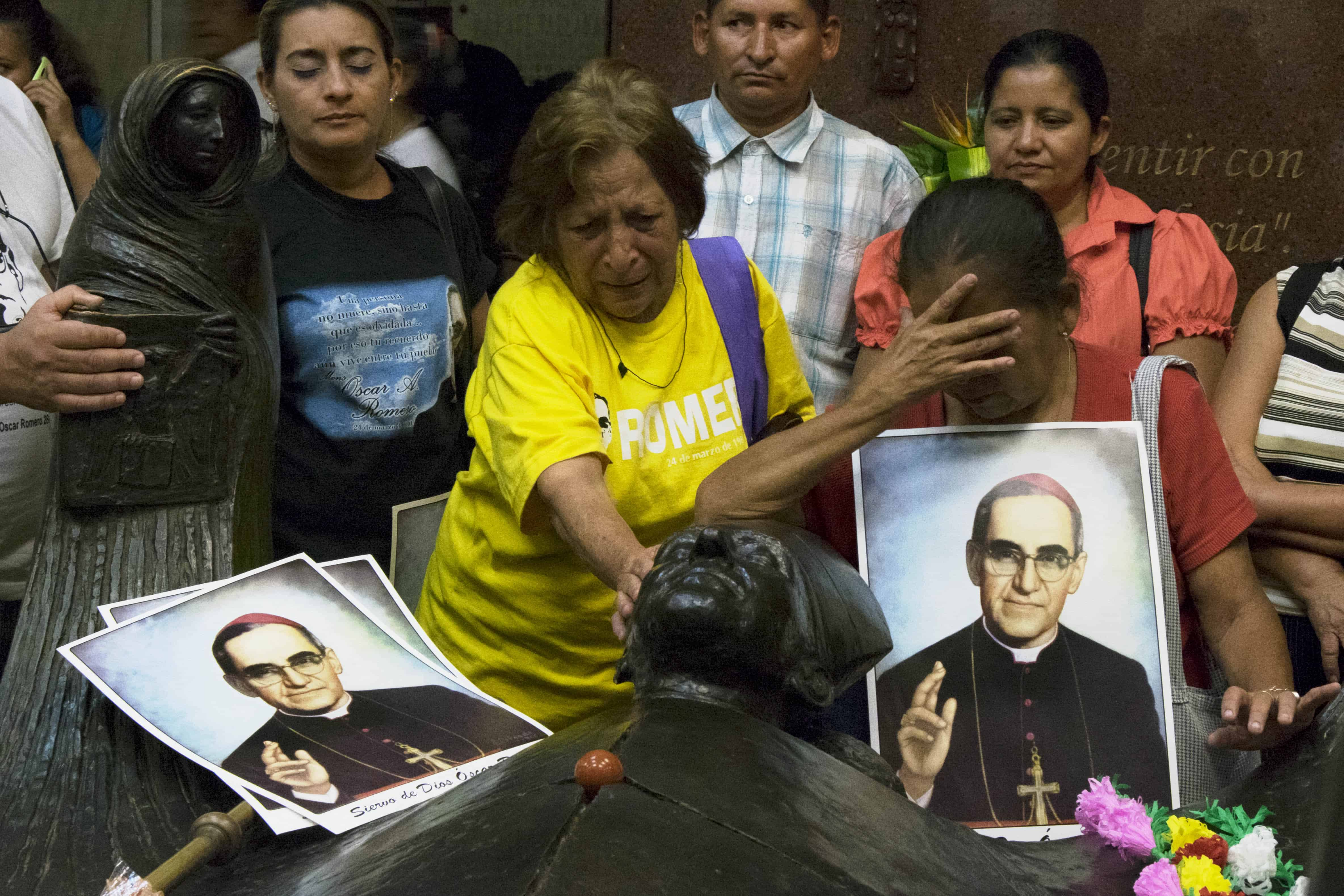 Luz Gloria Levas (in yellow), 72, cries at the tomb of Archbishop Oscar Romero in San Salvador, March 24, 2015.