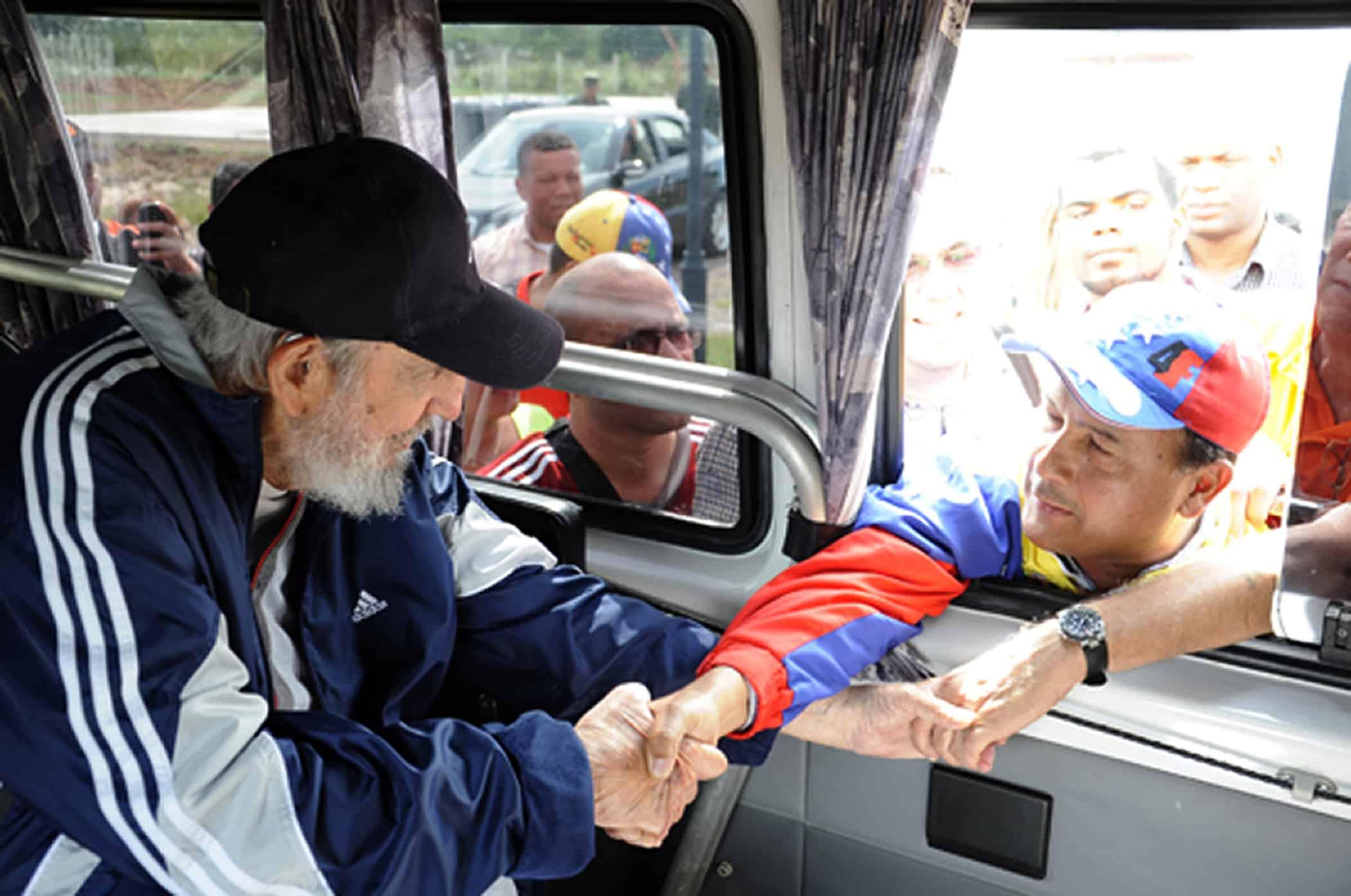 Former Cuban President Fidel Castro greets a member of a Venezuelan delegation.
