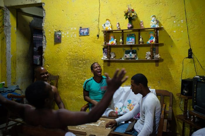 In the poor neighborhood of Juruquey in Camaguey, Cuba, shown on February 3, Yasmany Garcia, 26, in green, screams with excitement at the end of a round of dominos with his friends at his home. Camaguey is Cuba's  third largest city with more than 321,000 residents.