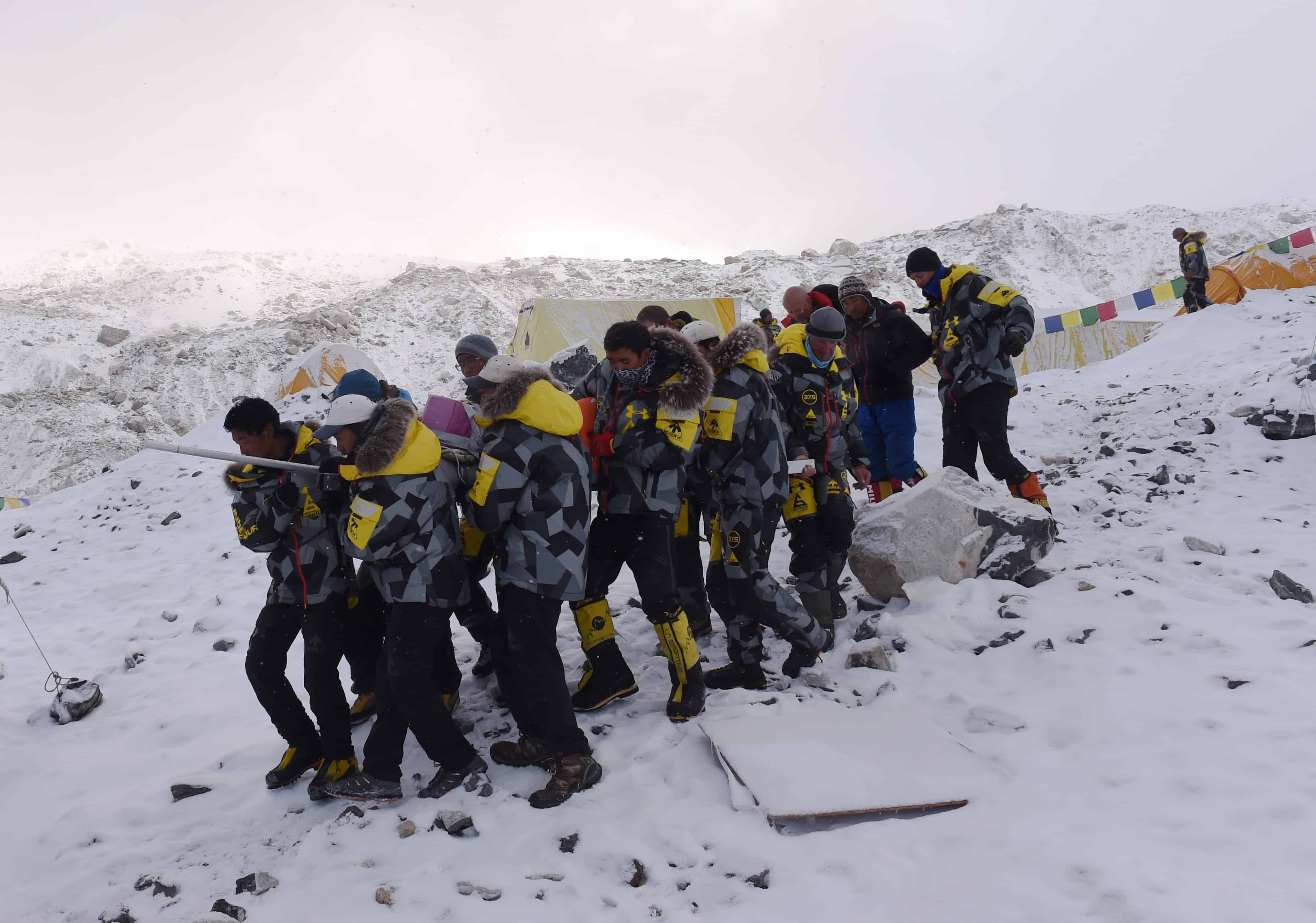 An injured person is carried by rescue members to be airlifted by rescue helicopter at Everest Base Camp on April 26, 2015, a day after an avalanche triggered by an earthquake devastated the camp. Rescuers in Nepal are searching frantically for survivors of a huge quake on April 25, that killed nearly 2,000, digging through rubble in the devastated capital Kathmandu and airlifting victims of an avalanche at Everest base Camp.