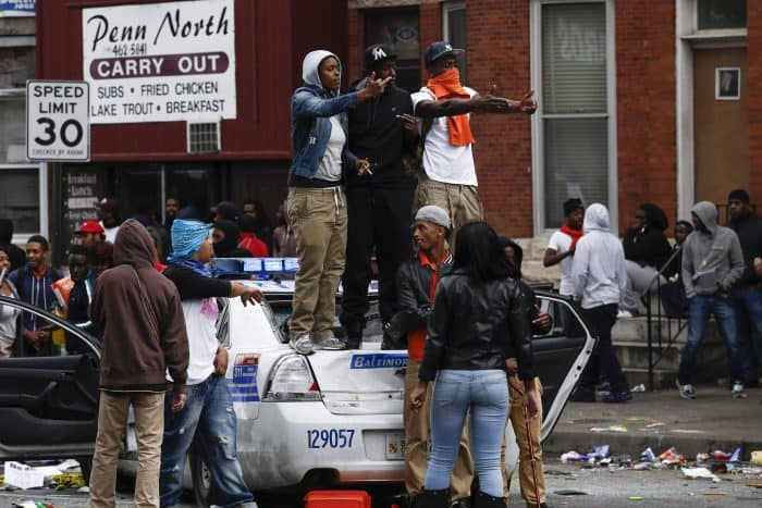 People stand on a damaged Baltimore Police car.
