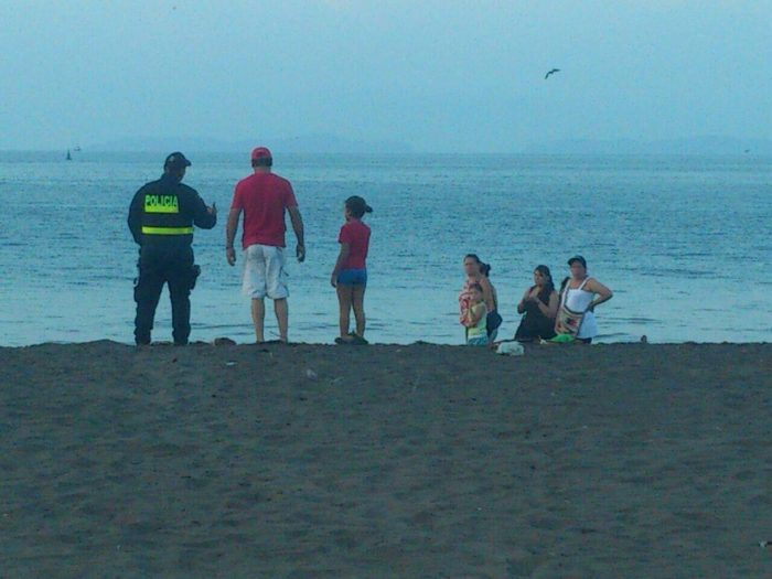 A police officer stands watch on a beach.