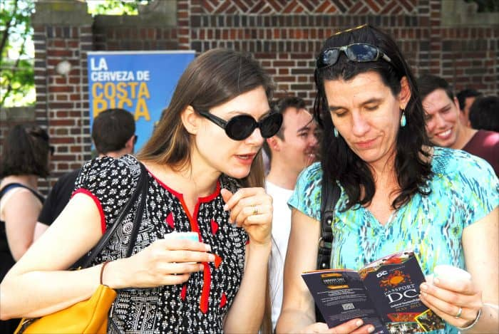 From left, Shelley McGinnis and Jessica Sahota, both visiting from California, consult a guide to Passport DC festivities Saturday, May 2, while relaxing at the Embassy of Costa Rica.