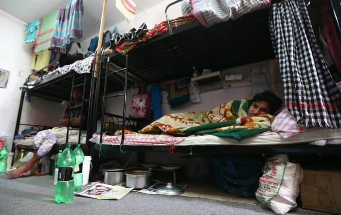 Mubarak, a laborer from Bangladesh, rests in his bedroom at a private camp housing foreign workers in Doha.