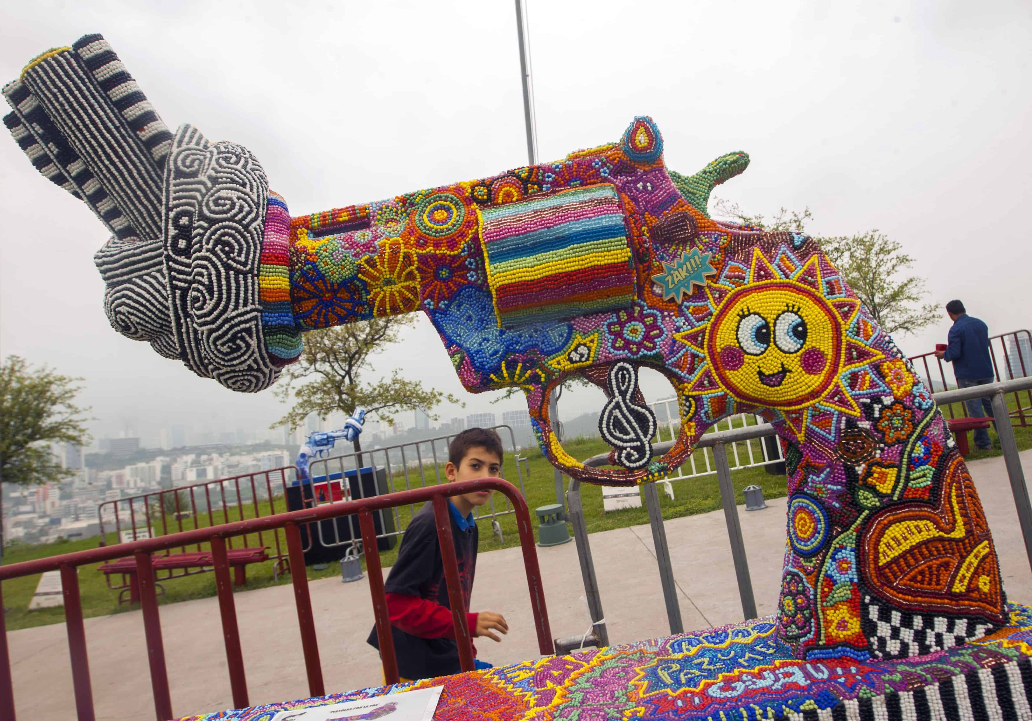 "A boy looks at one of the sculptures of an exhibition called ""Guns for Peace"" at Bishopric Hill in Monterrey, Nuevo León, Mexico."