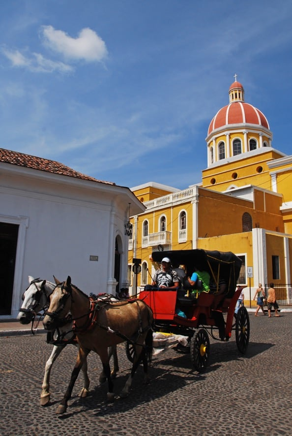 A horse and buggy in front the beautiful yellow cathedral in Granada, Nicaragua.