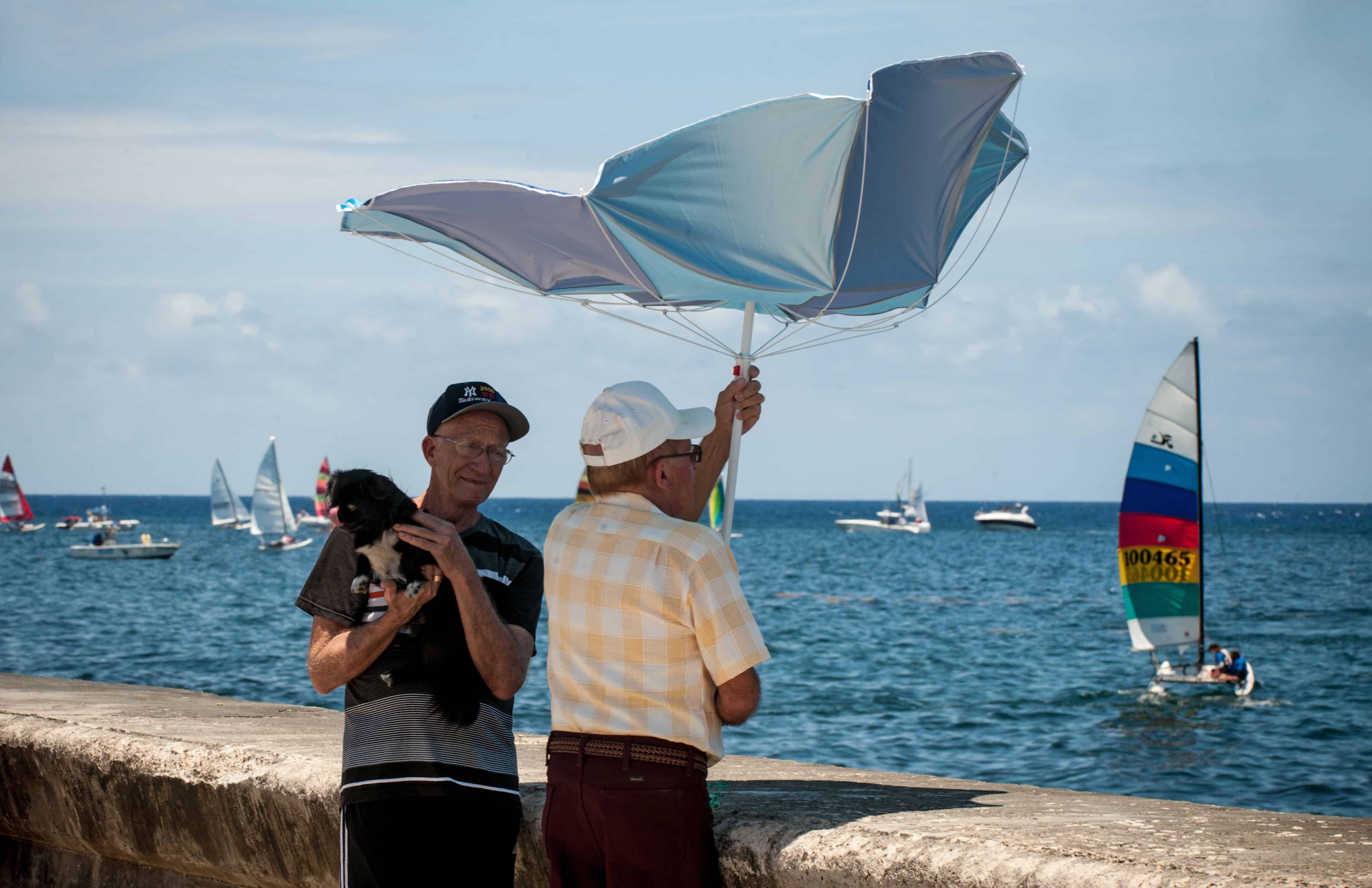 Men watch the Havana Challenge regatta from the city's Malecón on May 19, 2015.