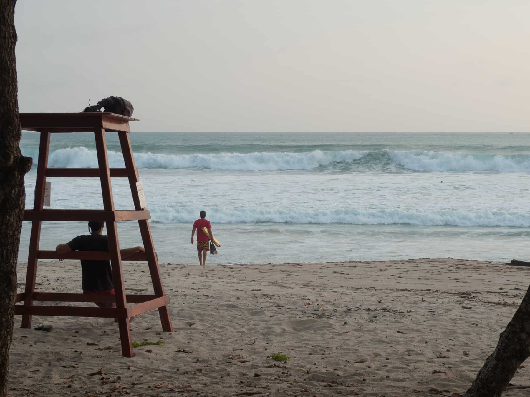 A Santa Teresa lifeguard stands at the water's edge.