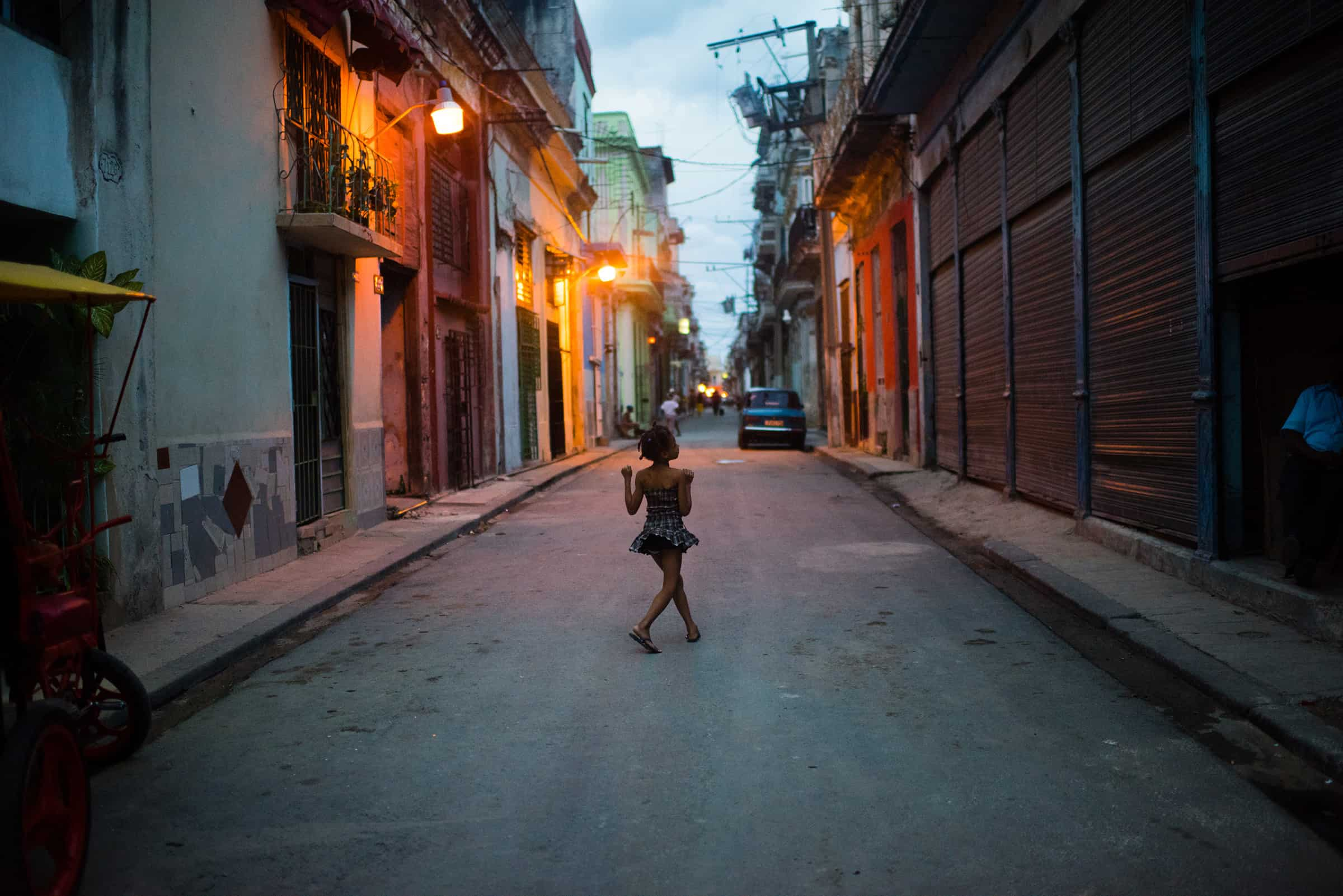 A young girl walks down San Ignacio street in Old Havana as the sun sets.