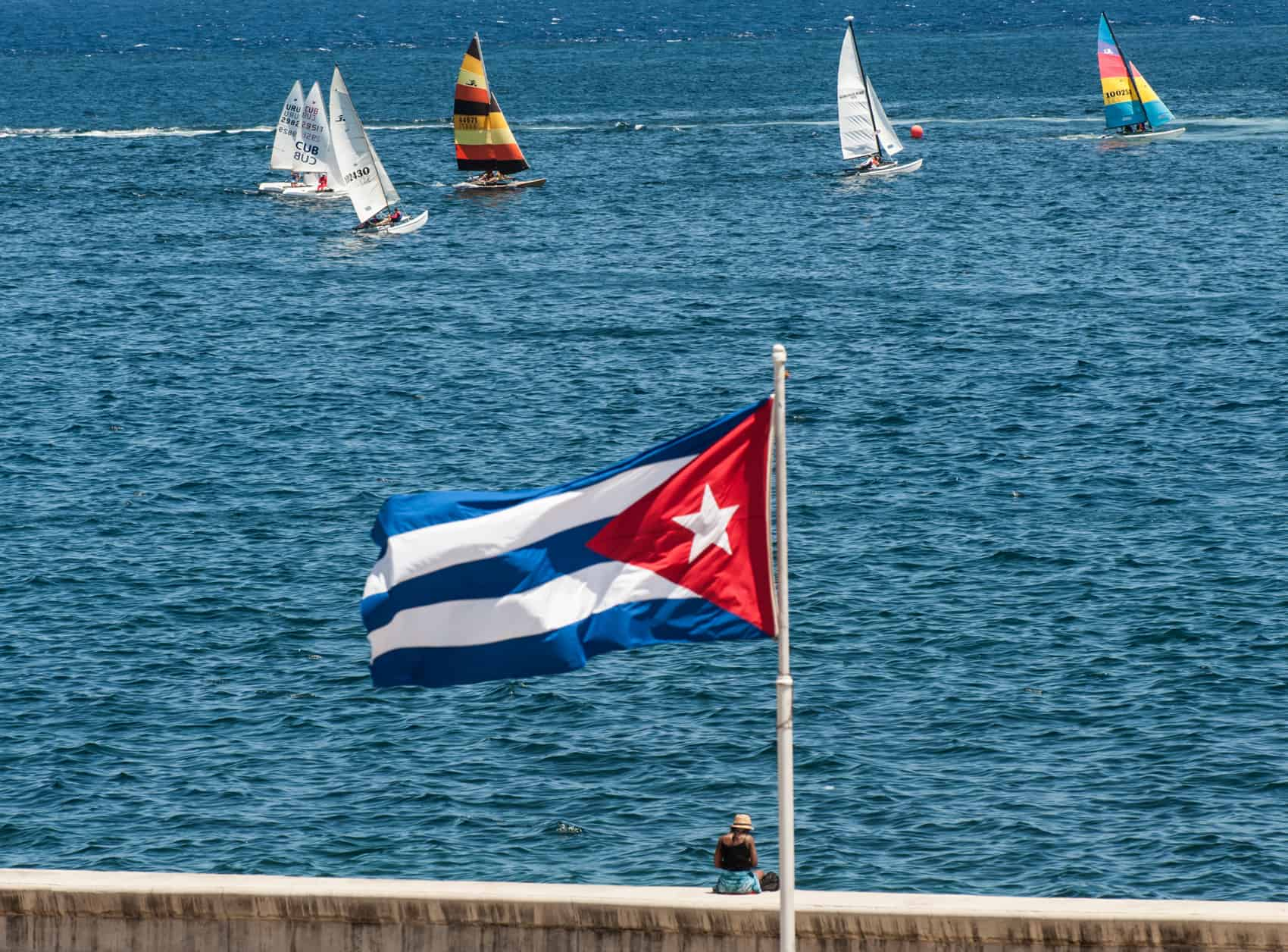 A Cuban national flag flutters as participants of the Havana Challenge regatta compete in Havana.