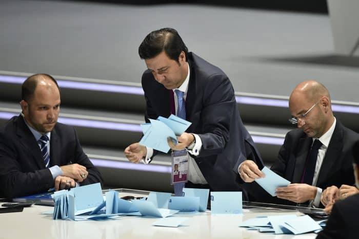 Officials sift through ballots .