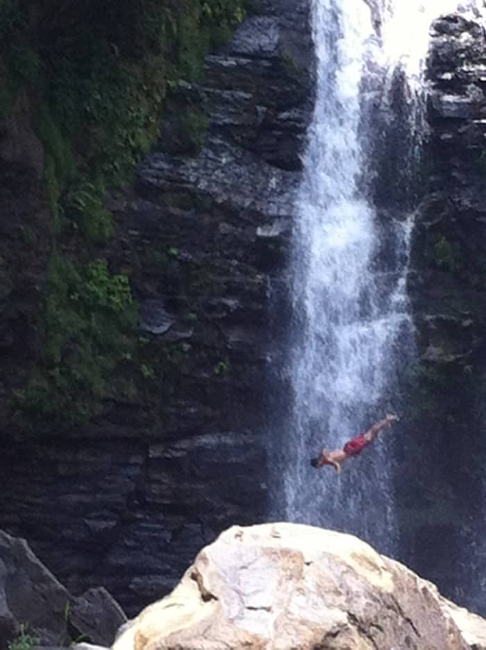 A tour guide dives off Nauyaca Waterfall.