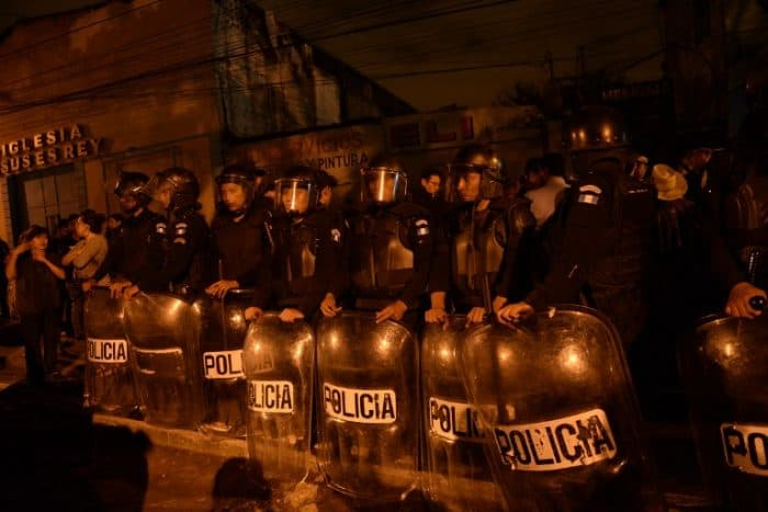 Riot police stand guard as indigenous people protest for the release of other protesters being held inside a bus by the National Civil Police after they participated in demonstrations to demand the resignation of Guatemalan President Otto Perez Molina as a corruption scandal rocks the government, in Guatemala City late on June 13, 2015.