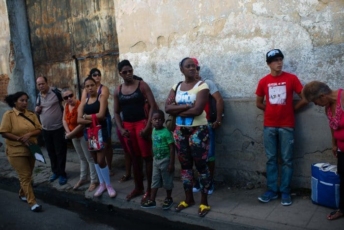 A group of people wait anxiously in Camaguey for public transportation.
